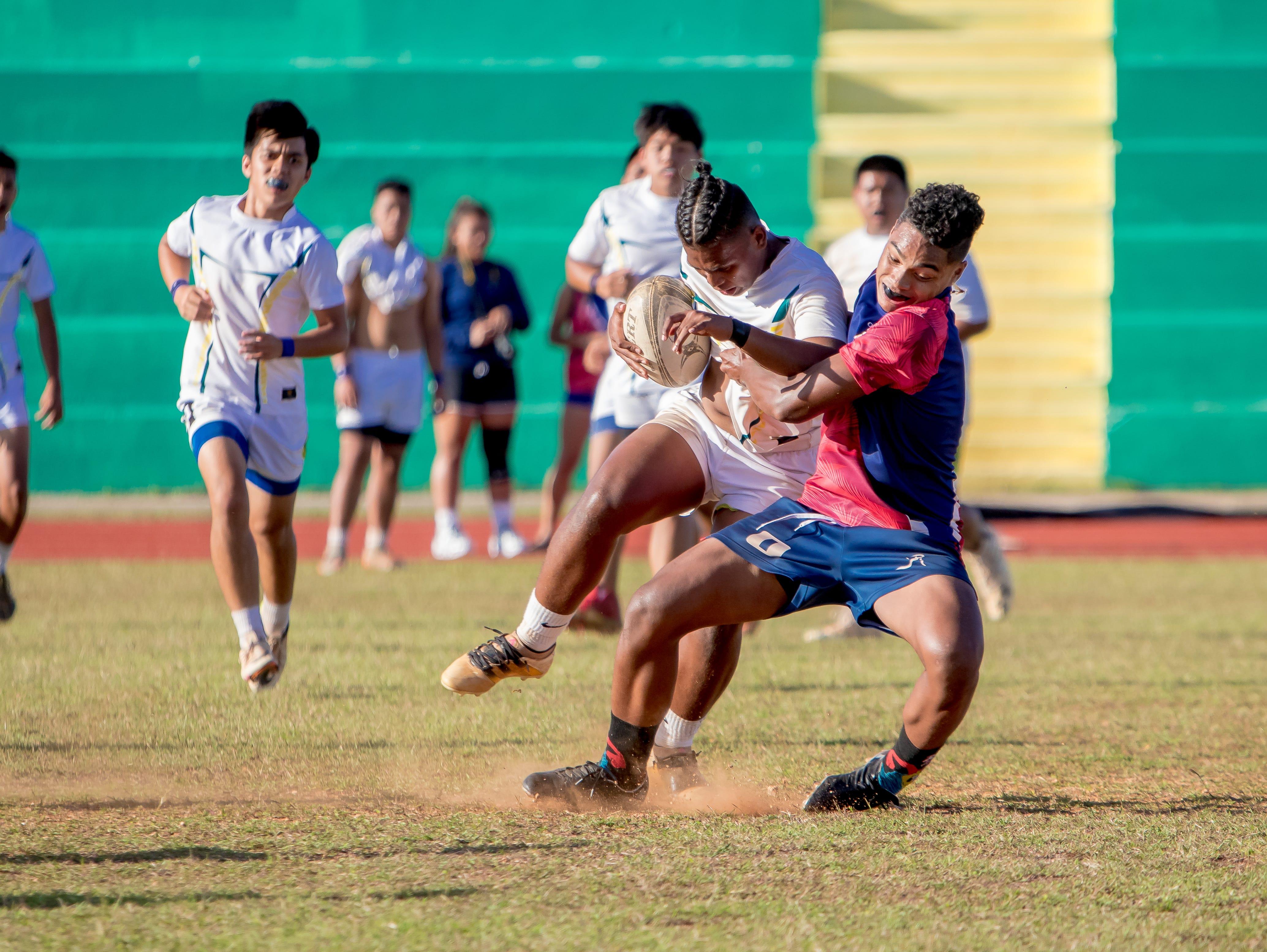 A John F. Kennedy High School rugger gets tackled by an Okkodo High School player during an IIAAG/GRFU Boys Rugby match at Ramsey Field on March 6.