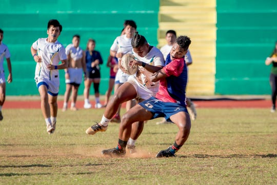 A John F. Kennedy High School rugger gets tackled by an Okkodo High School player during an IIAAG/GRFU Boys Rugby match at Ramsey Field on March 6.