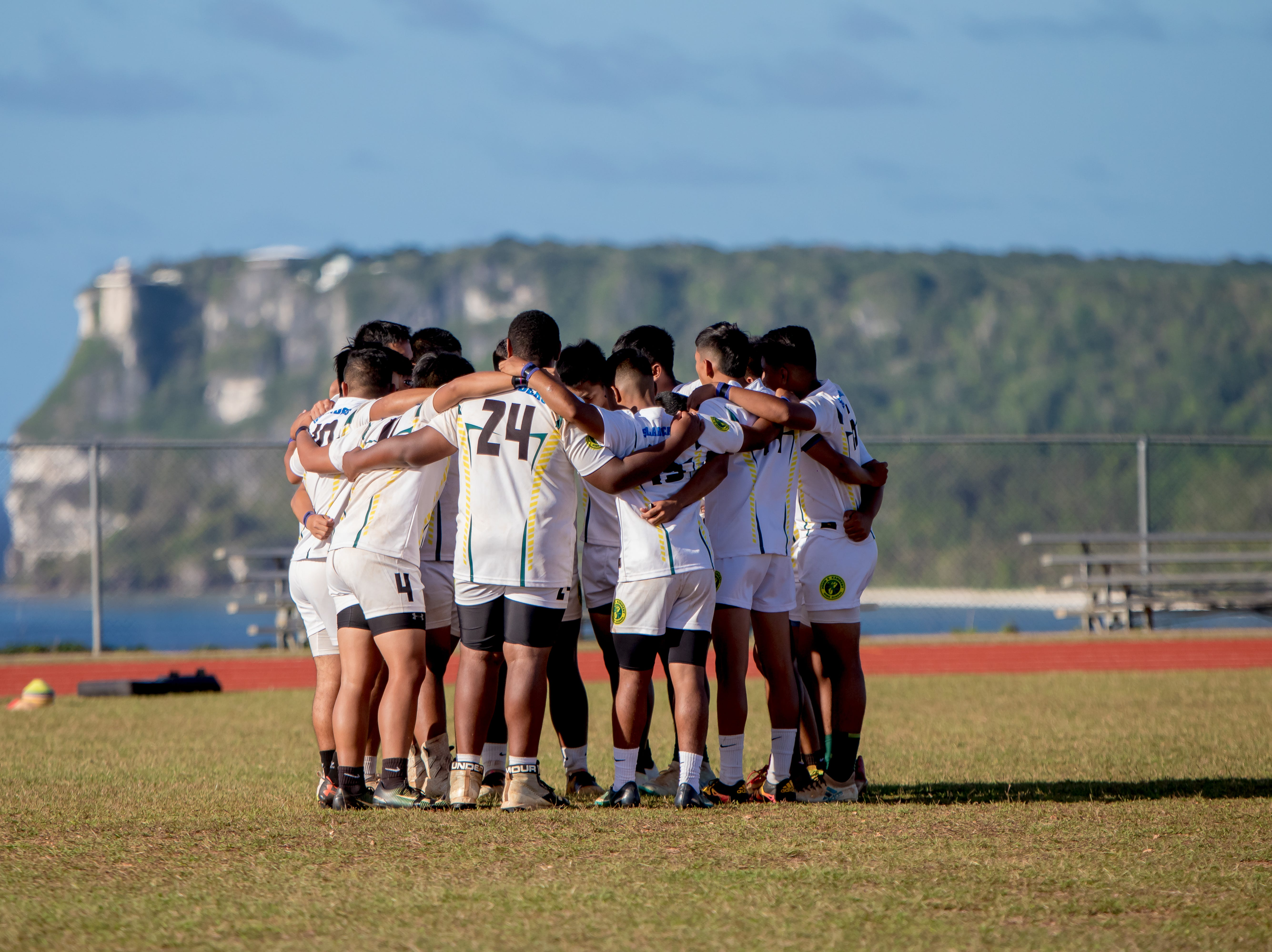 John F. Kennedy High School rugby players huddle before the match against Okkodo High School in an IIAAG/GRFU Boys Rugby contest at Ramsey Field on March 6.