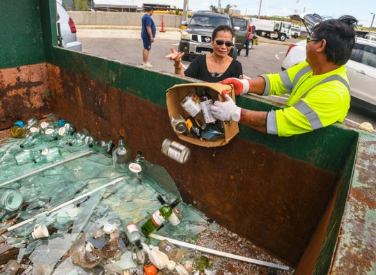 Guam Solid Waste Authority sanitation worker Gerald Castro assists a customer in emptying a box of glass bottles into a recycling bin at the Harmon Residential Transfer Station on Thursday, March 7, 2019.