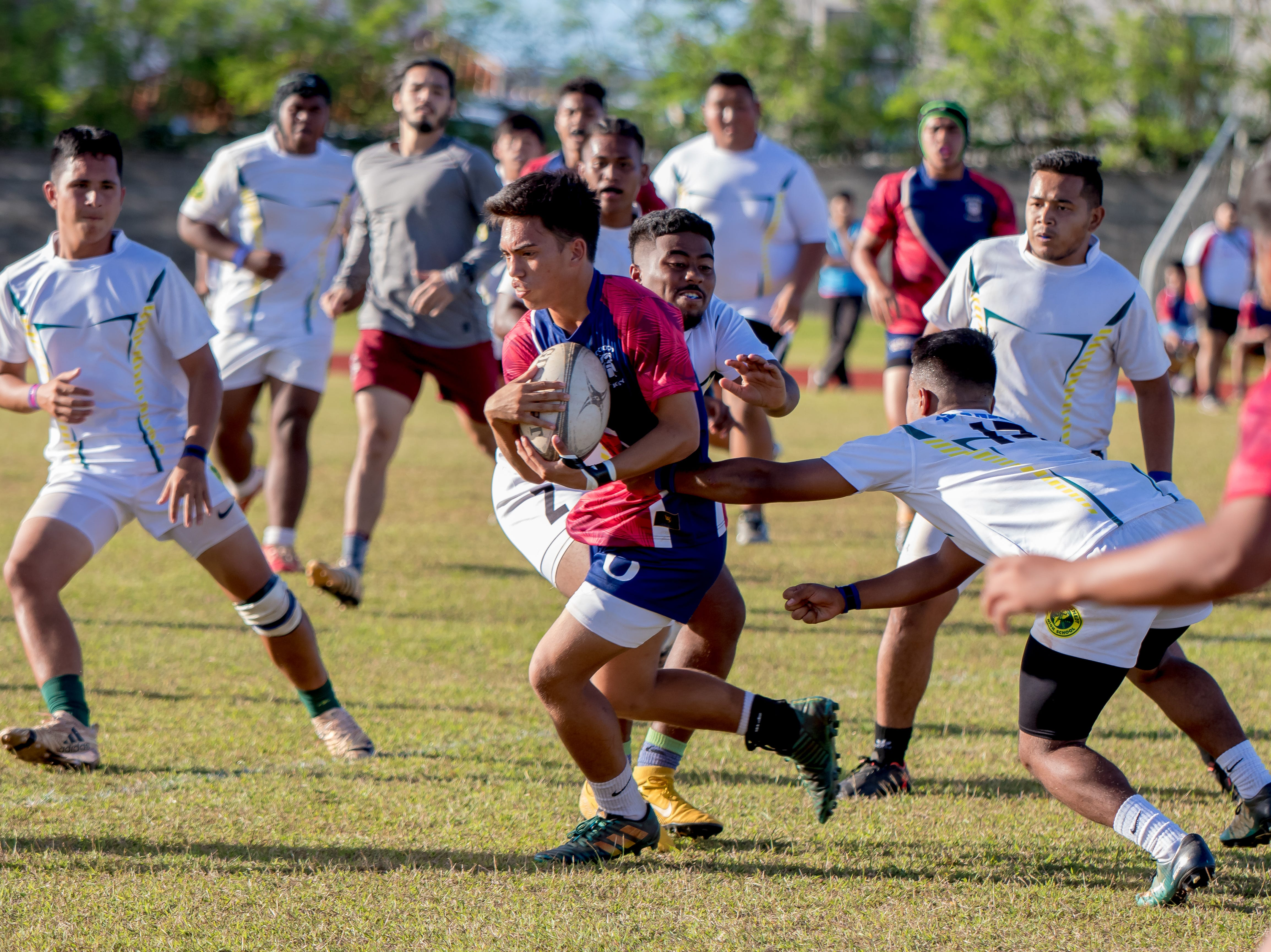 A Bulldog is surrounded by Islanders as he tries to evade the defenders during an IIAAG/GRFU Boys Rugby match at Ramsey Field on March 6.