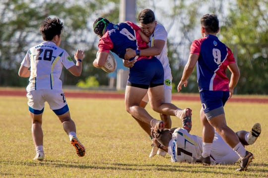 A Bulldog is tackled by an Islander during an IIAAG/GRFU Boys Rugby match at Ramsey Field on March 6.