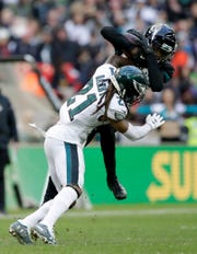 Philadelphia Eagles cornerback Ronald Darby (21) tackles Jacksonville Jaguars wide receiver D.J. Chark (17) during the second half of an NFL football game at Wembley stadium in London, Sunday, Oct. 28, 2018. (AP Photo/Matt Dunham)