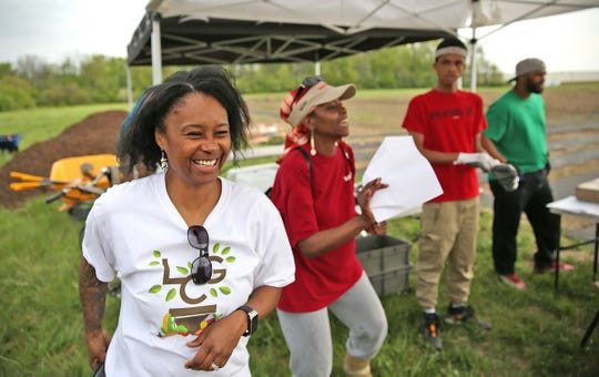 Sharrona Moore, left, laughs while giving directions to Lawrence Community Gardens volunteers on the east side of Indianapolis. The six-acre plot is used to grow food for the Lawrence community.