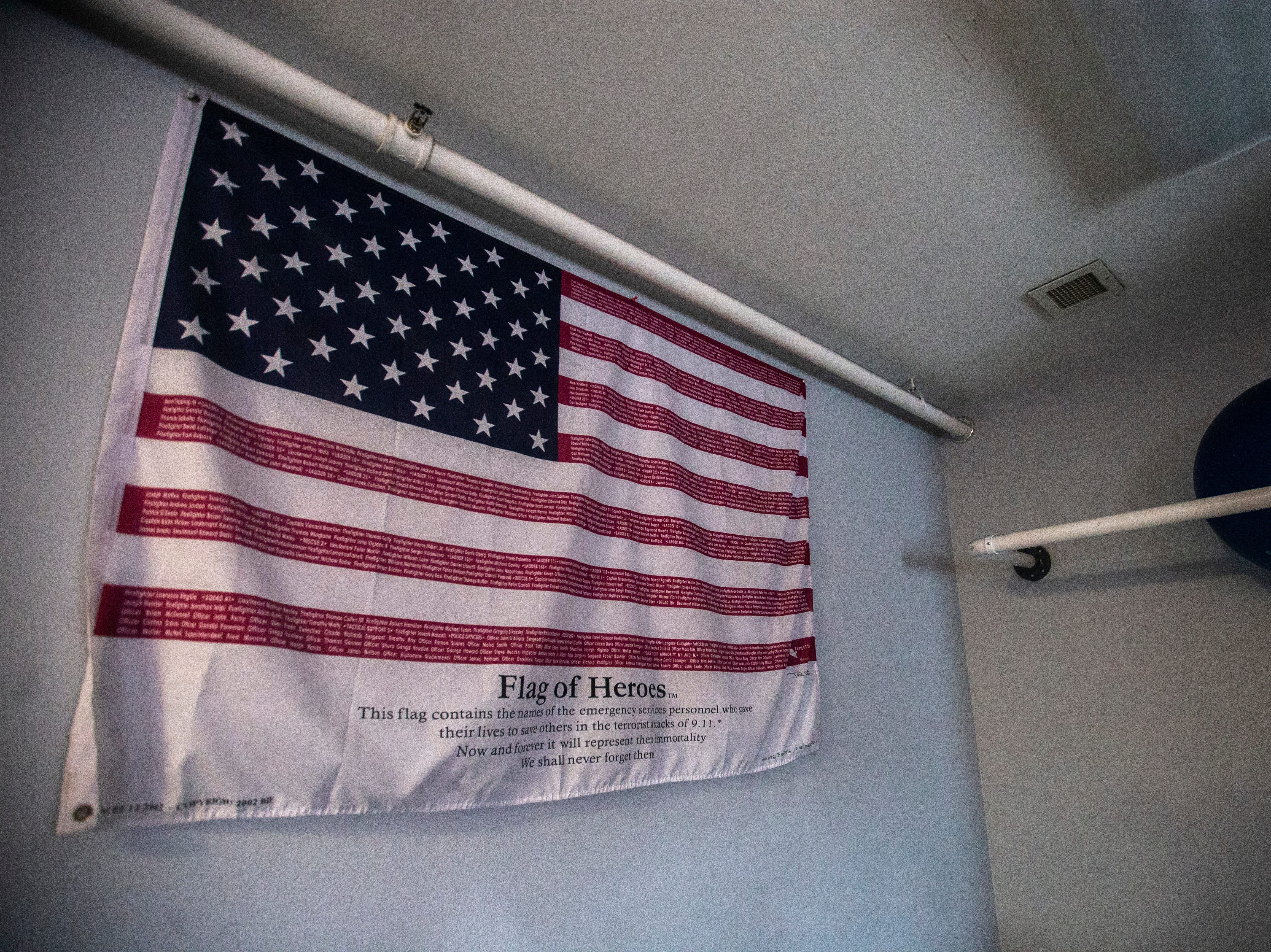 "A ""Flag of heroes"" featuring the names of emergency responders who died during the terrorist attacks on 9/11 in the red stripes of the American flag hangs in an exercise room on Thursday, March 7, 2019, inside Fire Station No. 1, at 10 South Gilbert Street in downtown Iowa City, Iowa."