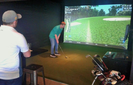 New fans of The Leaderboard indoor golf bar in North Liberty include Trevor O'Neill, general manager of Quail Creek Golf Course, who is preparing a chip shot at a simulated Myrtle Beach hole in this photo.  He and Chad Wilson, left, could be seen in league play recently at new business.