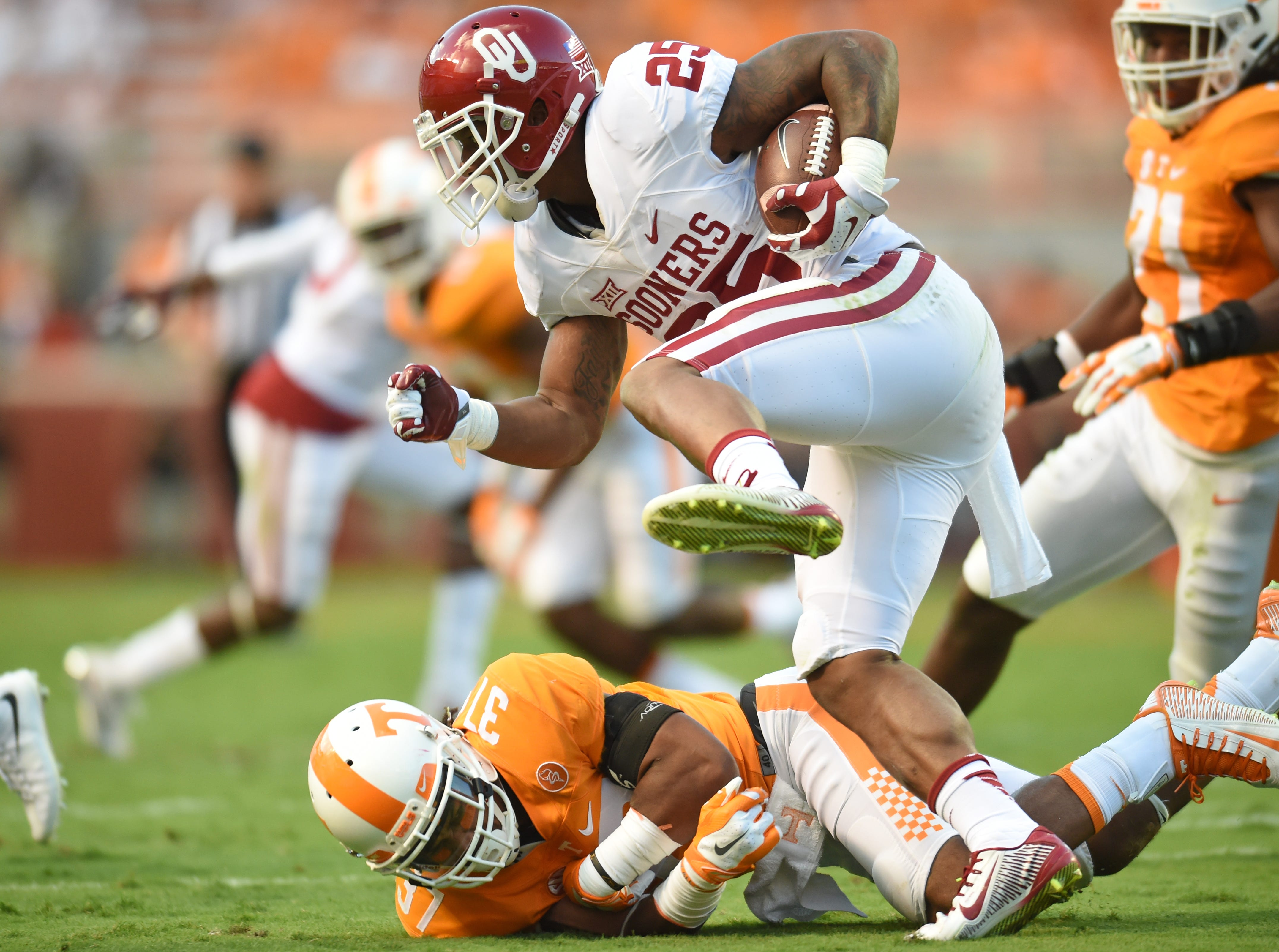 Oklahoma running back Joe Mixon (25) steps over an attempted tackle by Tennessee defensive back Brian Randolph (37) during the first half at Neyland Stadium on Saturday, Sept. 12, 2015 in Knoxville, Tenn.