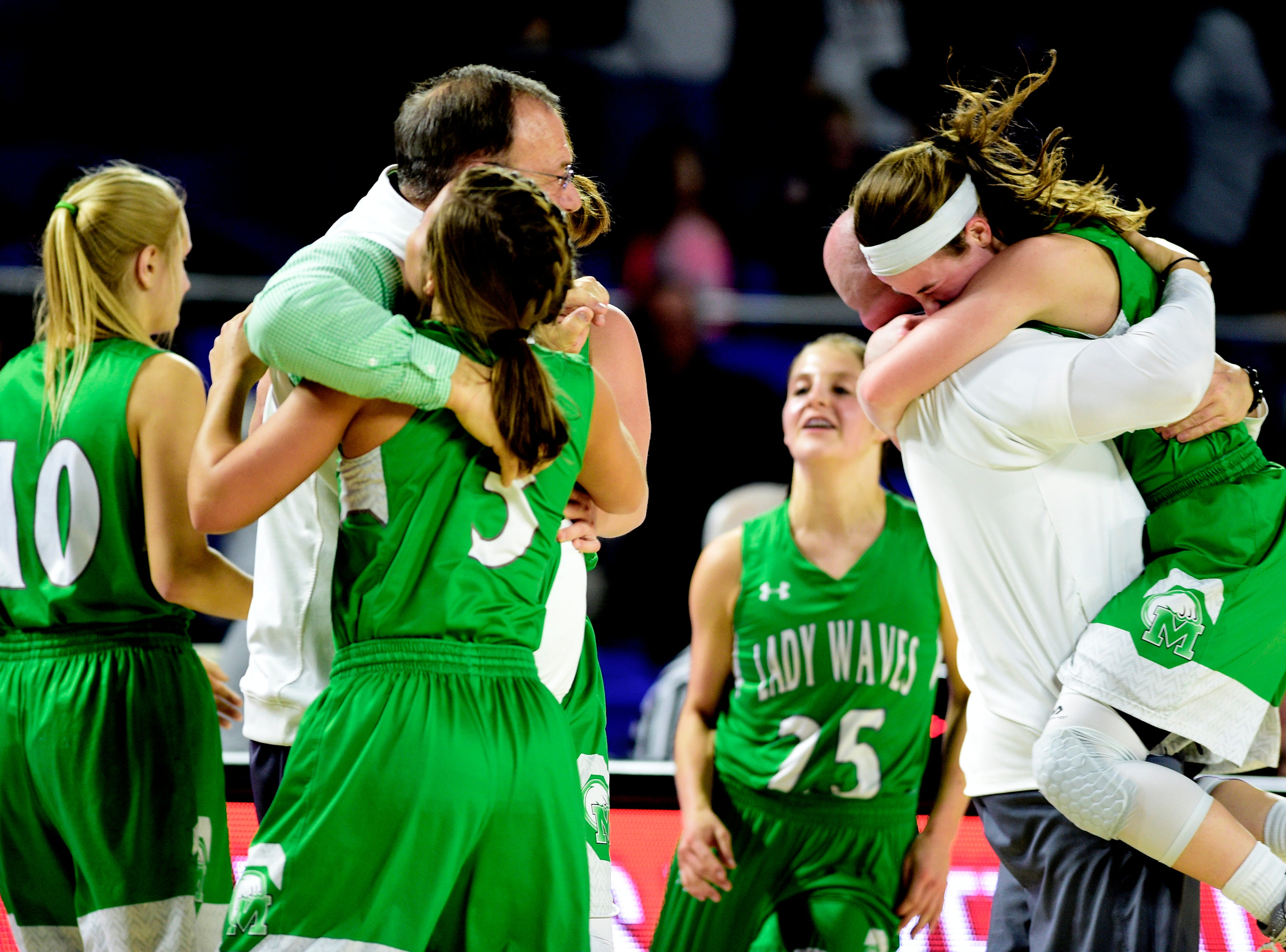 Midway's Caitlyn Ross (1) and Midway's Rebecca Lemasters (3) celebrate their win over Eagleville with their coaches at the TSSAA girls state tournament at the Murphy Center in Murfreesboro, Tennessee on Thursday, March 7, 2019.