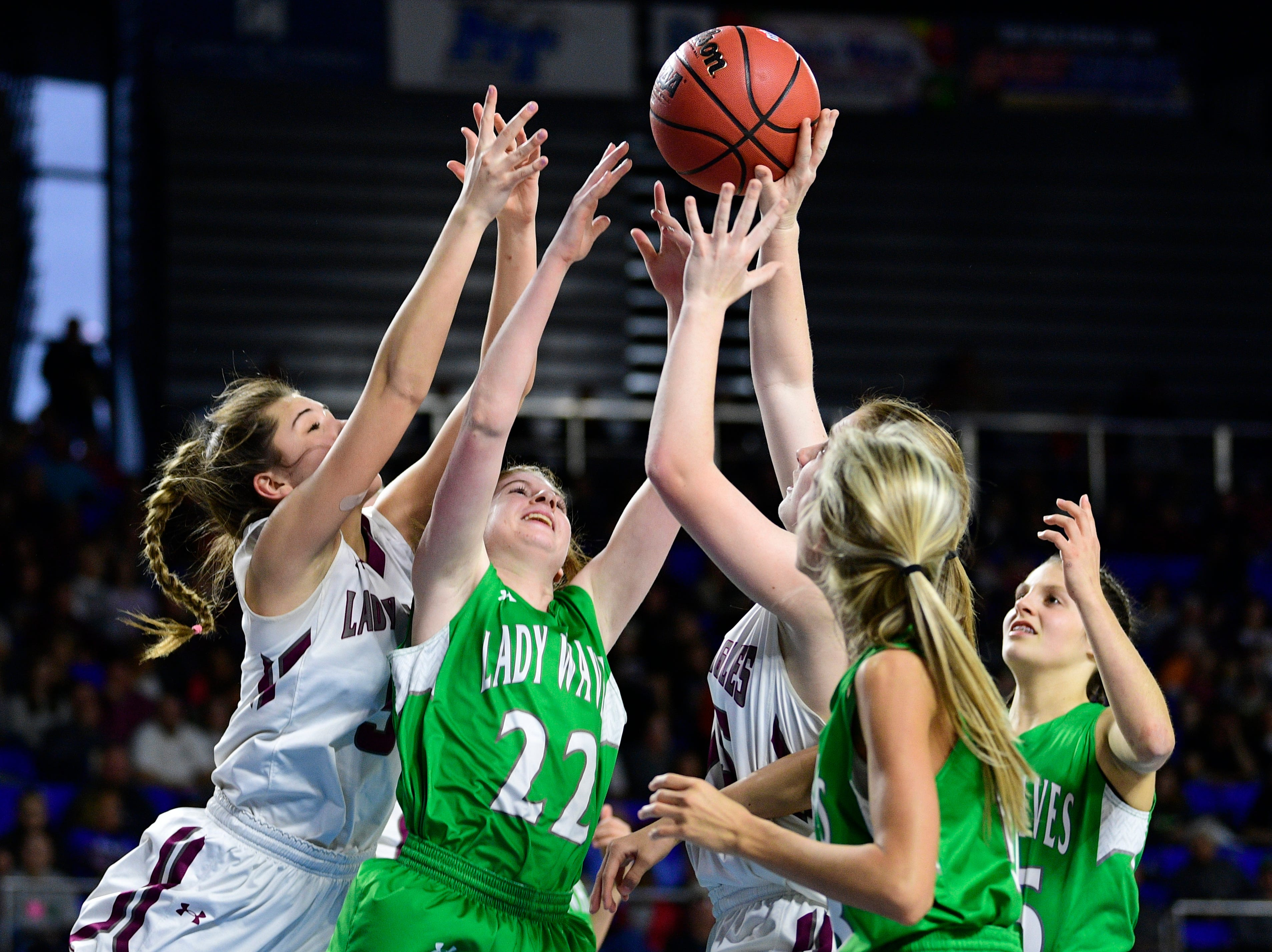 Players go after the ball during a game between Eagleville and Midway at the TSSAA girls state tournament at the Murphy Center in Murfreesboro, Tennessee on Thursday, March 7, 2019.