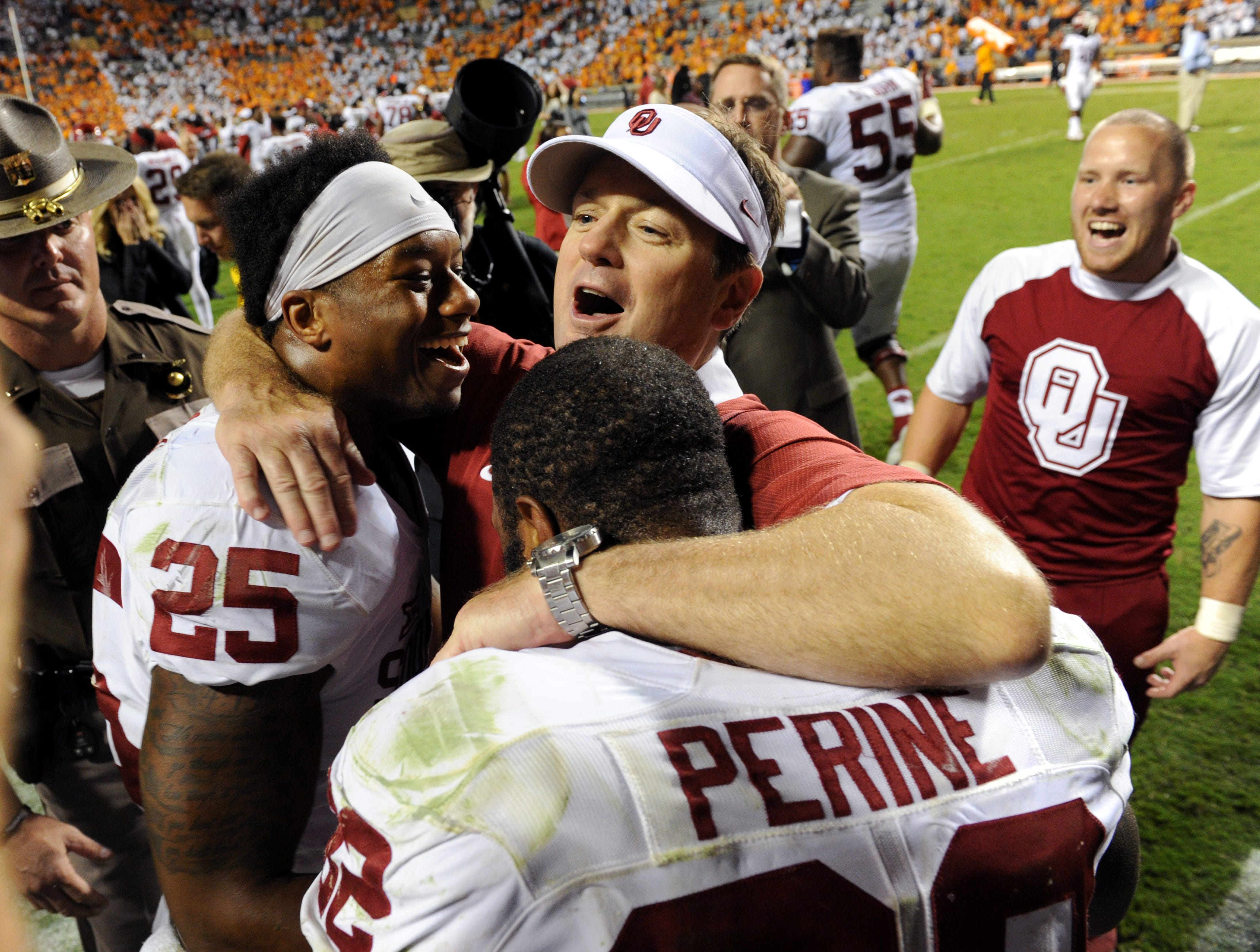 Oklahoma head coach Bob Stoops hugs Joe Mixon (25) and Samaje Perine (32) following their 31-24 victory over Tennessee in Neyland Stadium Saturday, Sep. 12, 2015.