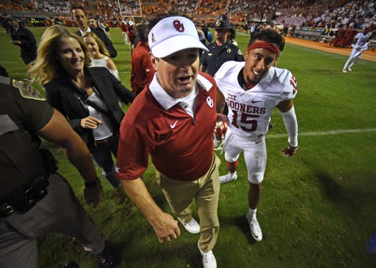 Oklahoma head coach Bob Stoops and Oklahoma wide Oklahoma cornerback Zack Sanchez (15), from left, celebrate after Sanchez's game-winning interception in Oklahoma's 31-24 victory over Tennessee in overtime at Neyland Stadium on Saturday, Sept. 12, 2015 in Knoxville, Tenn.