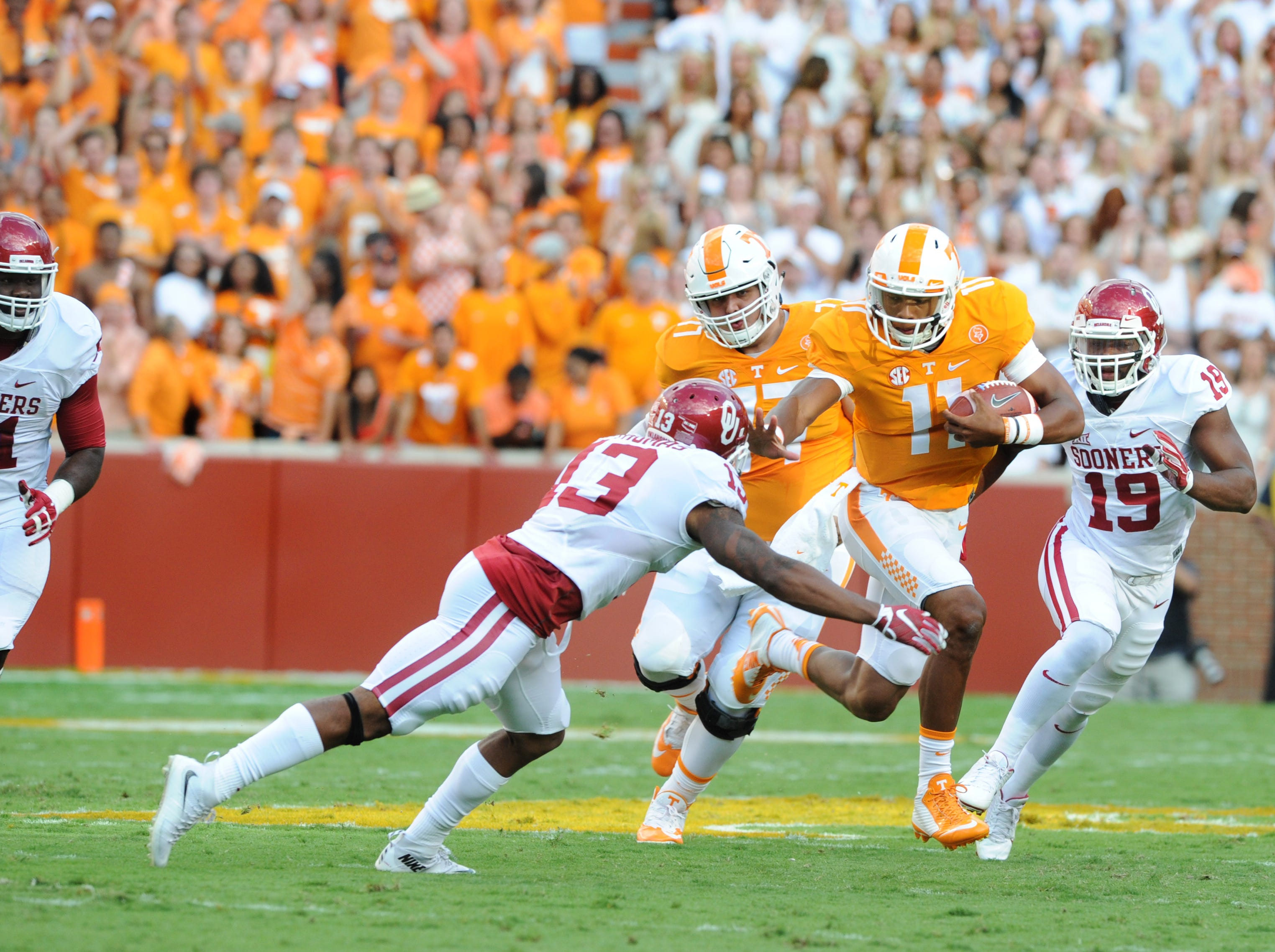 Tennessee quarterback Joshua Dobbs (11) pushes off an advance by Oklahoma safety Ahmad Thomas (13) during the first half at Neyland Stadium on Saturday, Sept. 12, 2015 in Knoxville, Tenn.