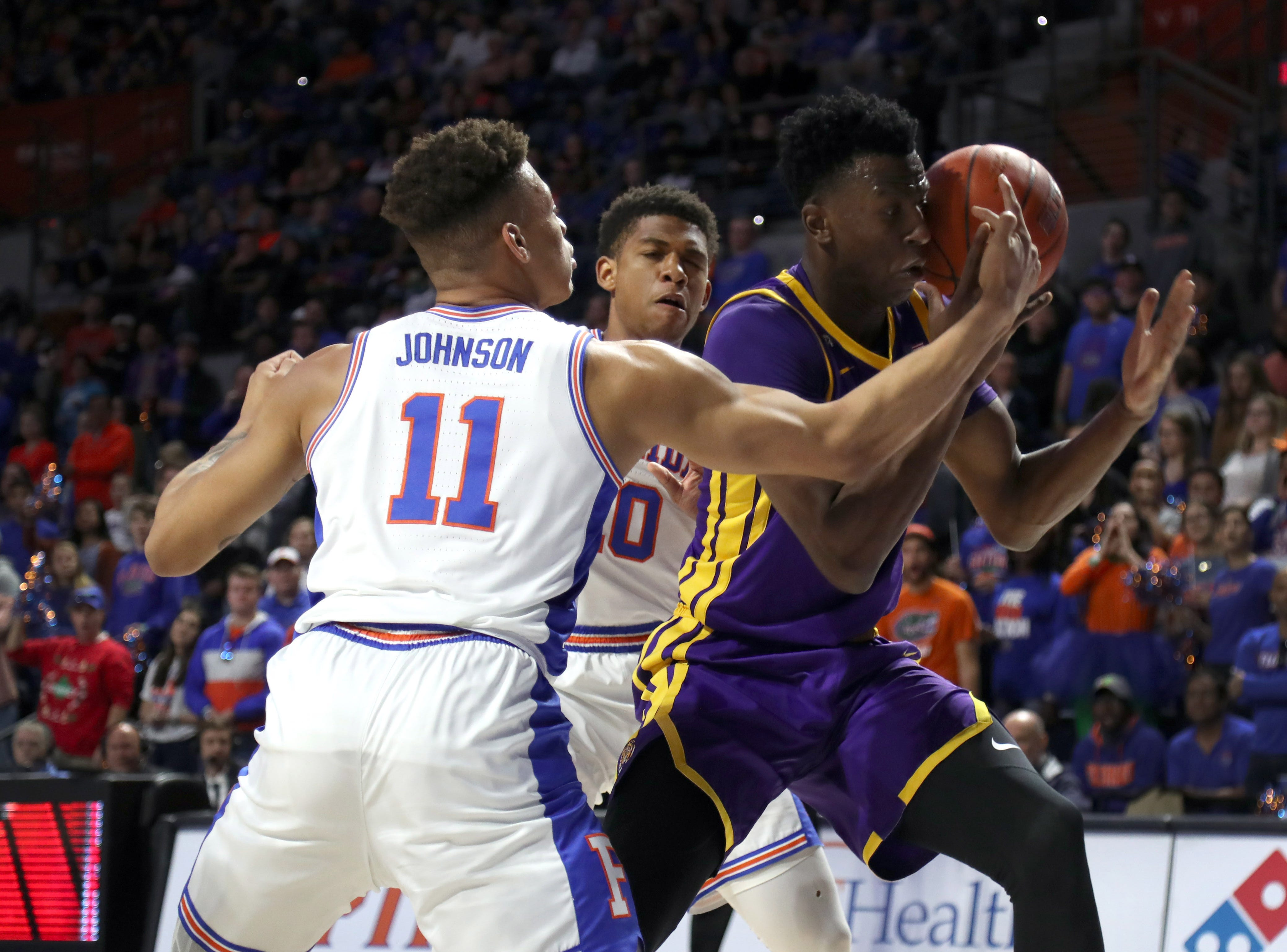 Mar 6, 2019; Gainesville, FL, USA; Florida Gators forward Keyontae Johnson (11) forces LSU Tigers forward Kavell Bigby-Williams (11) to turn the ball over during the first half at Exactech Arena. Mandatory Credit: Kim Klement-USA TODAY Sports
