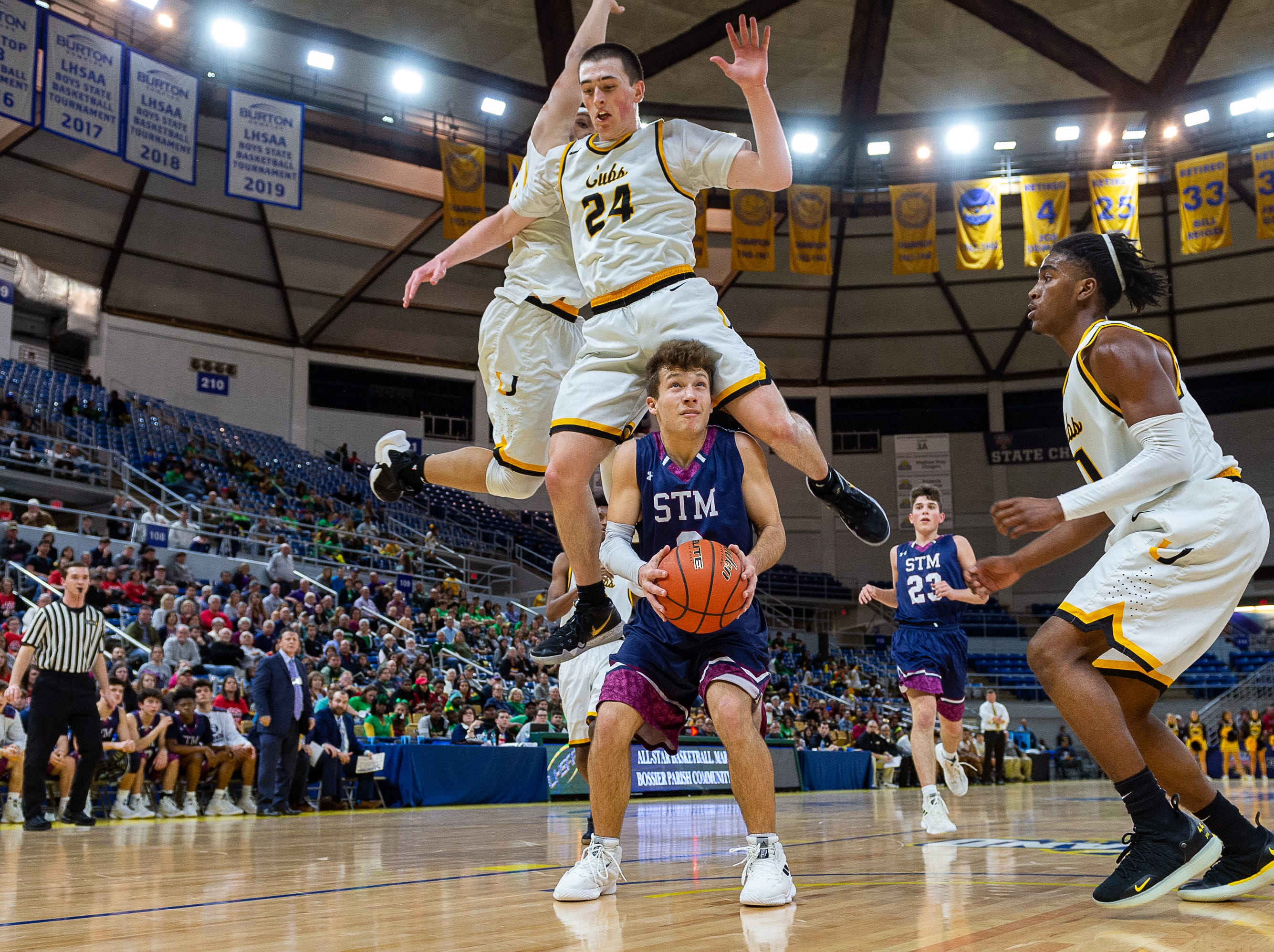 Grant Arceneaux is fouled under the basket as STM takes down University High in the semi final round of the LHSAA Basketball State Championships. Wednesday, March 6, 2019.