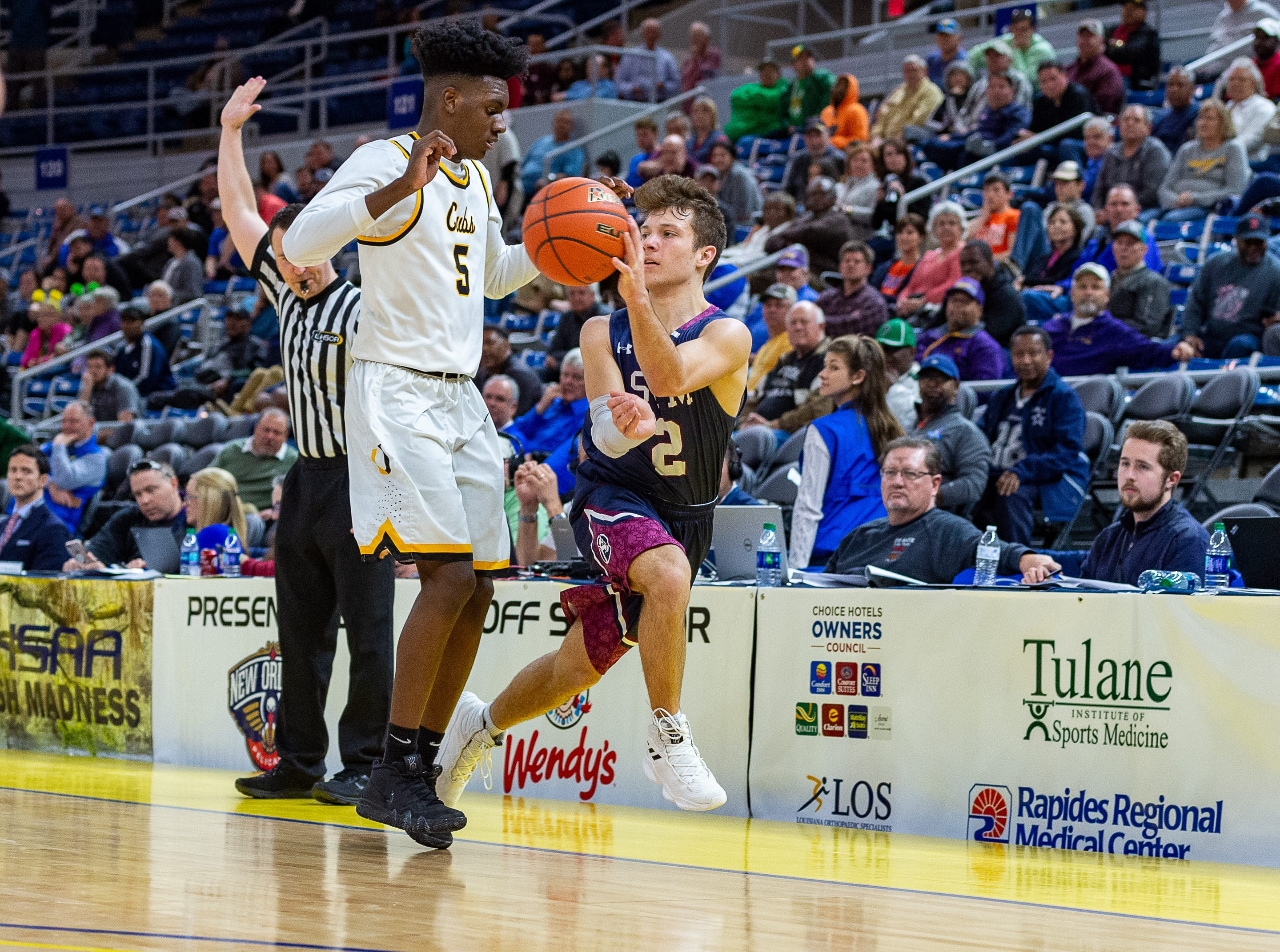 Grant Arceneaux passes the ball as STM takes down University High in the semi final round of the LHSAA Basketball State Championships. Wednesday, March 6, 2019.