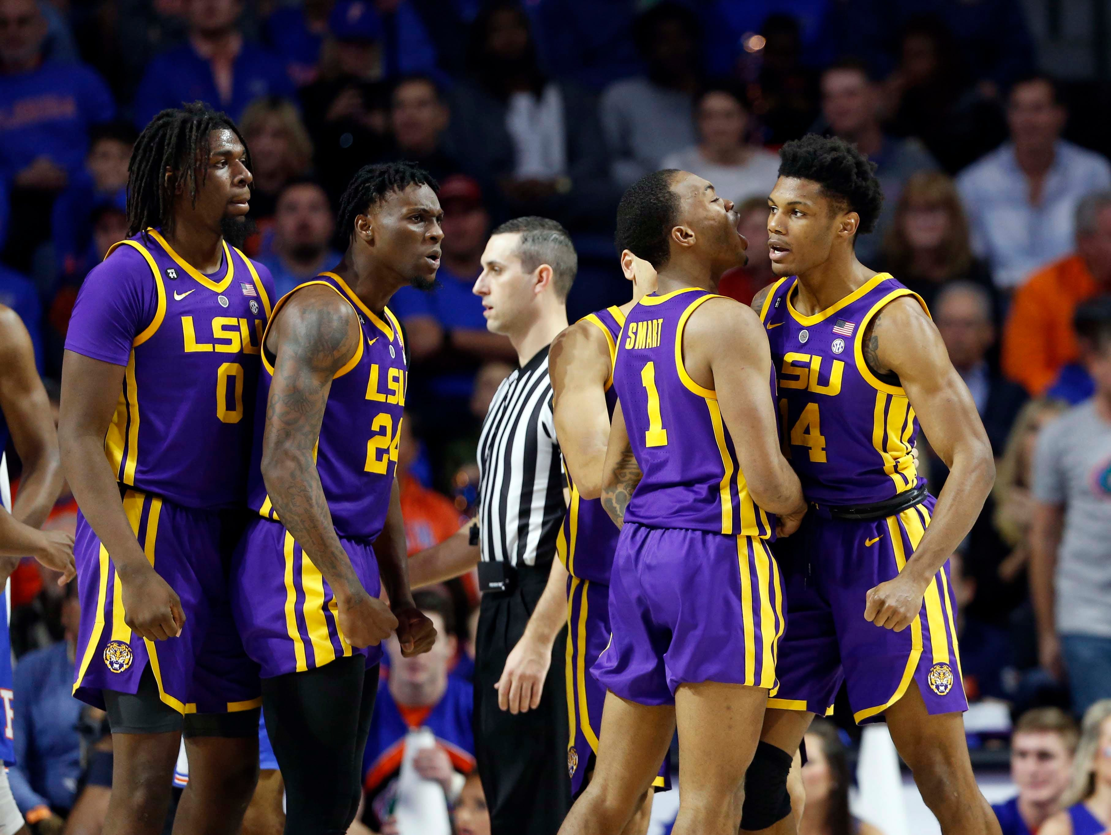 Mar 6, 2019; Gainesville, FL, USA; LSU Tigers guard Marlon Taylor (14), forward Emmitt Williams (24), guard Javonte Smart (1) and teammates celebrate against the Florida Gators during the second half at Exactech Arena. Mandatory Credit: Kim Klement-USA TODAY Sports