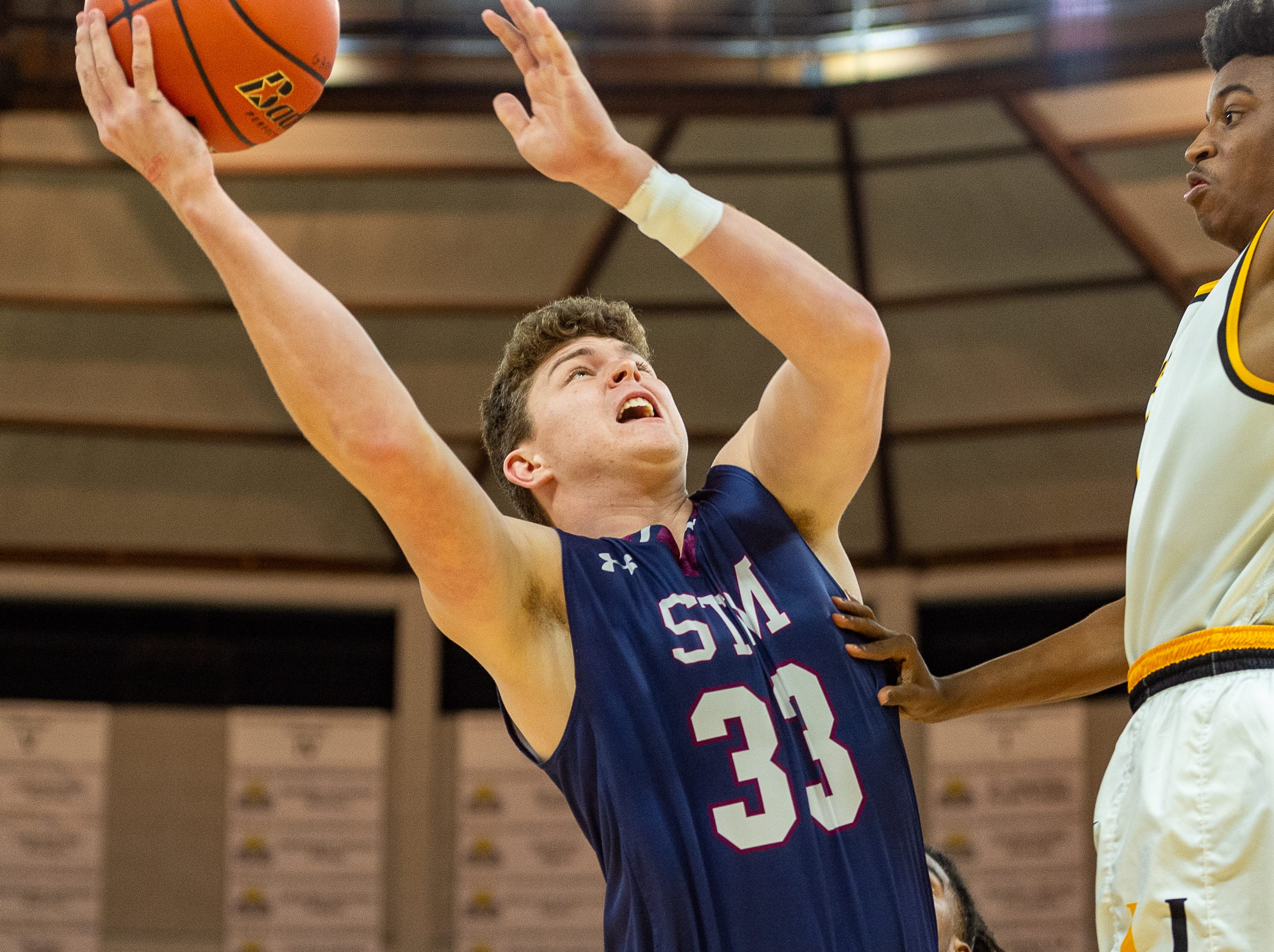 St. Thomas More's Caleb Holstein shoots the ball as STM takes down University High in the semifinal round of the LHSAA Division II basketball State Championships on Wednesday, March 6, 2019.