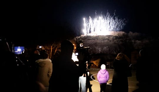 People watch and photograph as fireworks shoot off of Mount Pleasant to mark the first official night of it being illuminated by lights Wednesday, March 6, 2019, from Mount Pleasant Elementary in Lancaster.