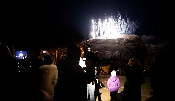 People watch and photograph as firework shoot off of Mount Pleasant to mark the first official night of it being illuminated by lights Wednesday, March 6, 2019, from Mount Pleasant Elementary in Lancaster.