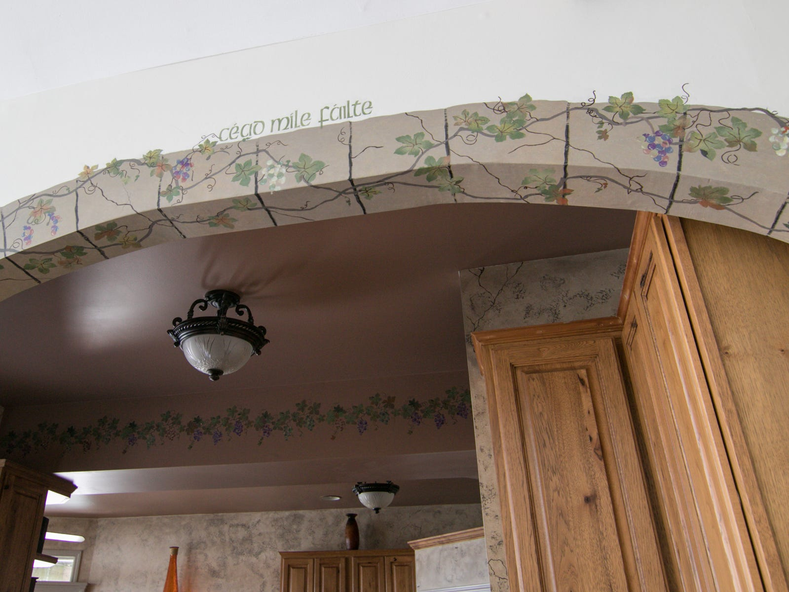 Hand-painted designs adorn the archway leading into the kitchen and dining room of the Olmsted home, shown Thursday, March 7, 2019.