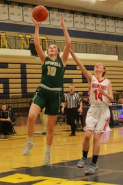 Howell's Kaylee Wendel (10) drives for two of her career-high 26 points while defended by Holly's Megan Strunk in a district basketball semifinal at Hartland on Wednesday, March 6, 2019.