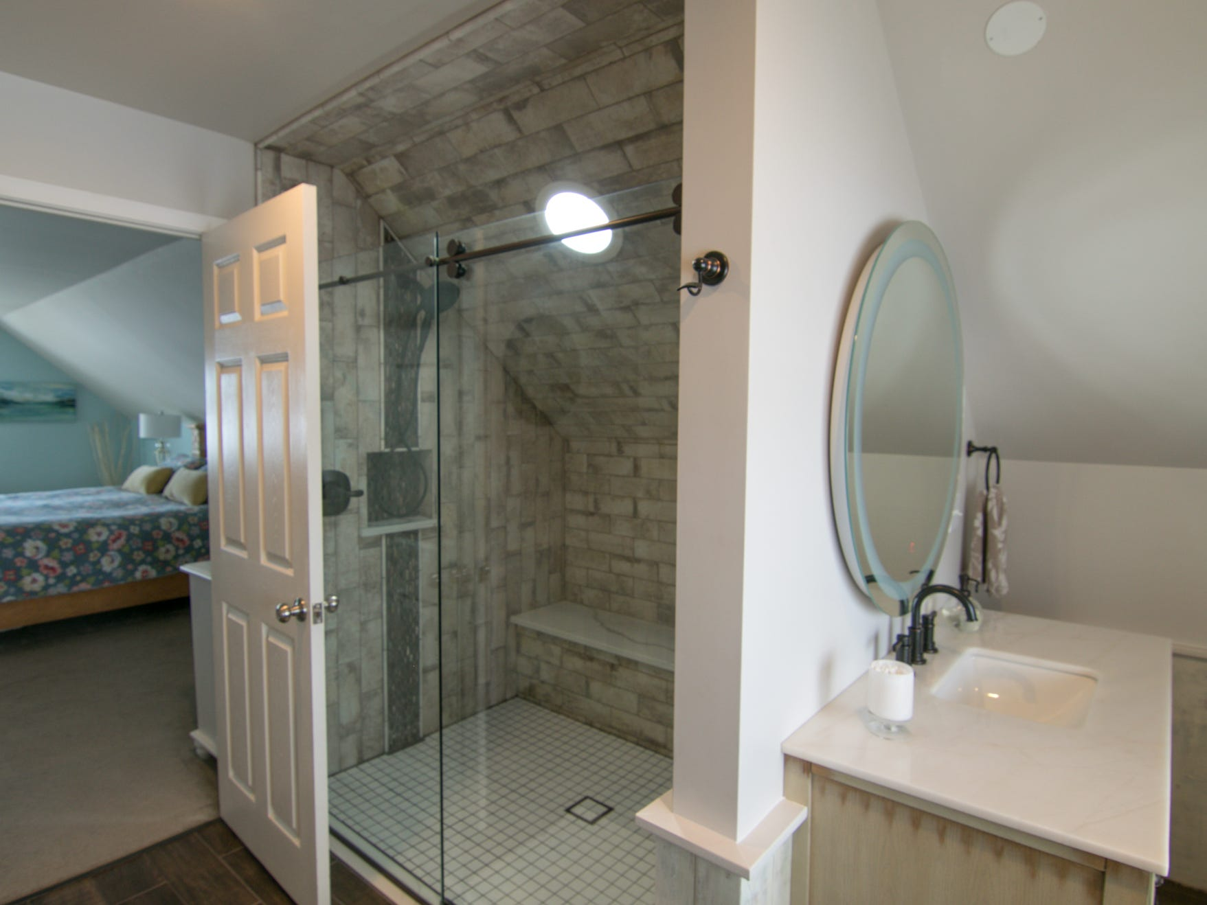 An ensuite bath adjoins one of two master bedrooms in the Olmsted home, shown Thursday, March 7, 2019.