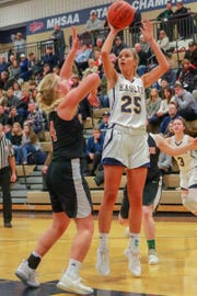 Hartland's Whitney Sollom puts up a shot over Fenton's Chloe Idoni in a 43-22 district semifinal basketball victory on Wednesday, March 6, 2019.
