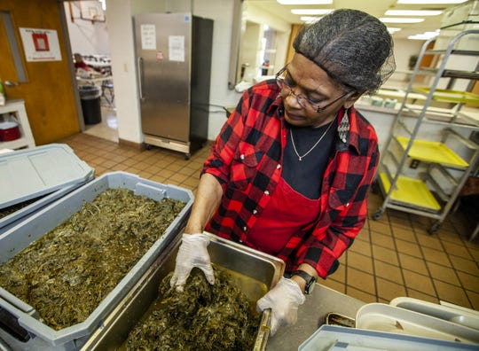 Ann Gardner readies a large batch of mixed greens in preparation for the St. Augustine fish fry. March 6, 2019.