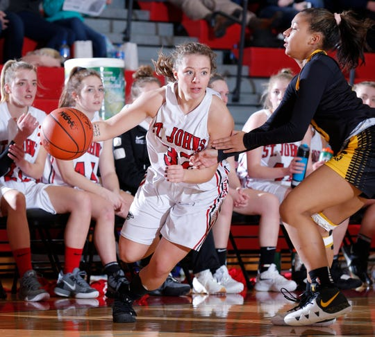 St. Johns' Madison Robbins, left, drives against Waverly's Jaida Thomas, Wednesday, March 6, 2019, in St. Johns, Mich. St. Johns won 61-29.