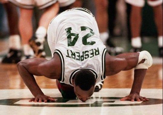 """Former Michigan State guard Shawn Respert kisses the Spartan """"S"""" at center court following his final game in 1995. (Margie Garrison/Lansing State Journal file)"""
