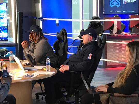 Grizz Gaming general manager Lang Whitaker (center) waits for the team's second-round pick to be announced during the NBA 2K League draft on Tuesday night