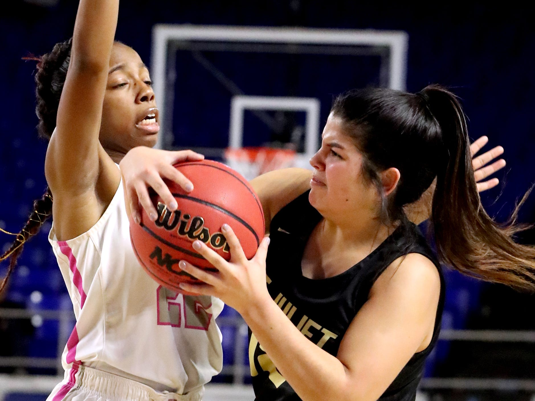 Mt. Juliet's Ryleigh Osborne (12) looks for a player to pass to as Houston's Nakiyah Westbrook (22) guards her during the quarterfinal round of the TSSAA Div. 1 Class AAA Girls State Tournament, on Wednesday, March 6, 2019, at Murphy Center in Murfreesboro, Tenn.