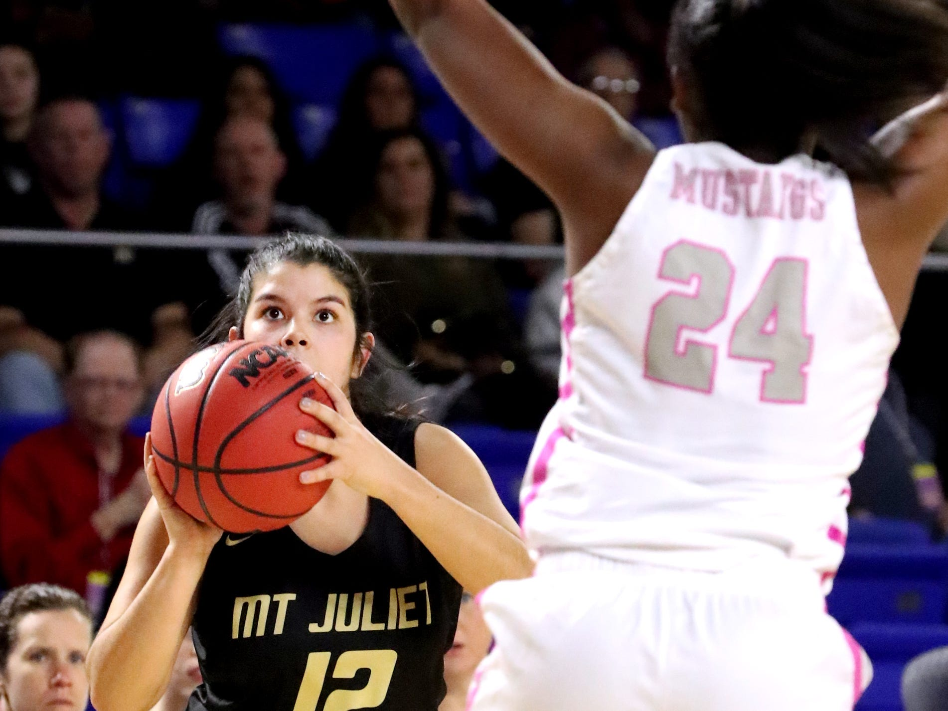 Mt. Juliet's Ryleigh Osborne (12) attempts a three point basket as Houston's Destinee Wells (24) guards her  a during the quarterfinal round of the TSSAA Div. 1 Class AAA Girls State Tournament, on Wednesday, March 6, 2019, at Murphy Center in Murfreesboro, Tenn.