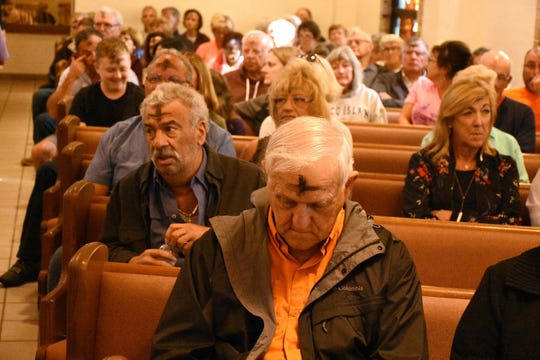 Sal Iannotta, left, returns to his pew at San Marco Catholic Church. Catholics on Marco Island and around the world, along with many other Christians, celebrated Ash Wednesday by attending mass and having a cross drawn on their foreheads in ashes.