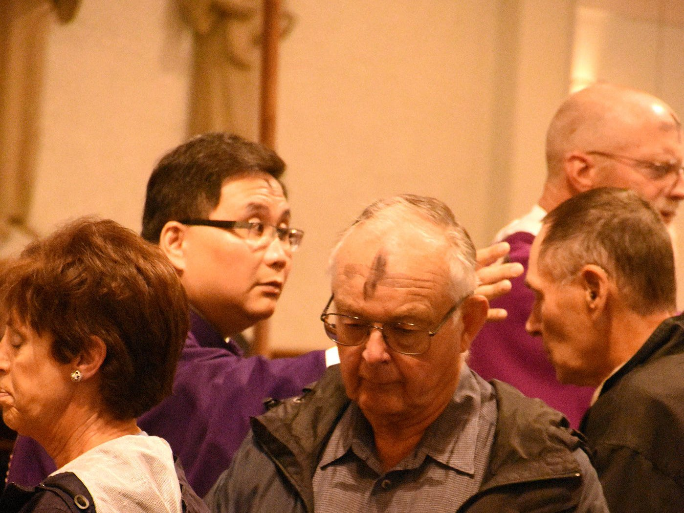 Rev. Duong Nguyen applies ashes to worshippers at San Marco Catholic Church. Catholics on Marco Island and around the world, along with many other Christians, celebrated Ash Wednesday by attending mass and having a cross drawn on their foreheads in ashes.