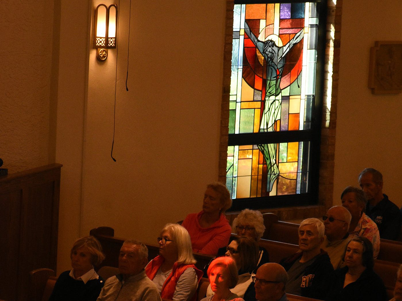 Light from stained glass windows bathes a parishioner. Catholics on Marco Island and around the world, along with many other Christians, celebrated Ash Wednesday by attending mass and having a cross drawn on their foreheads in ashes.