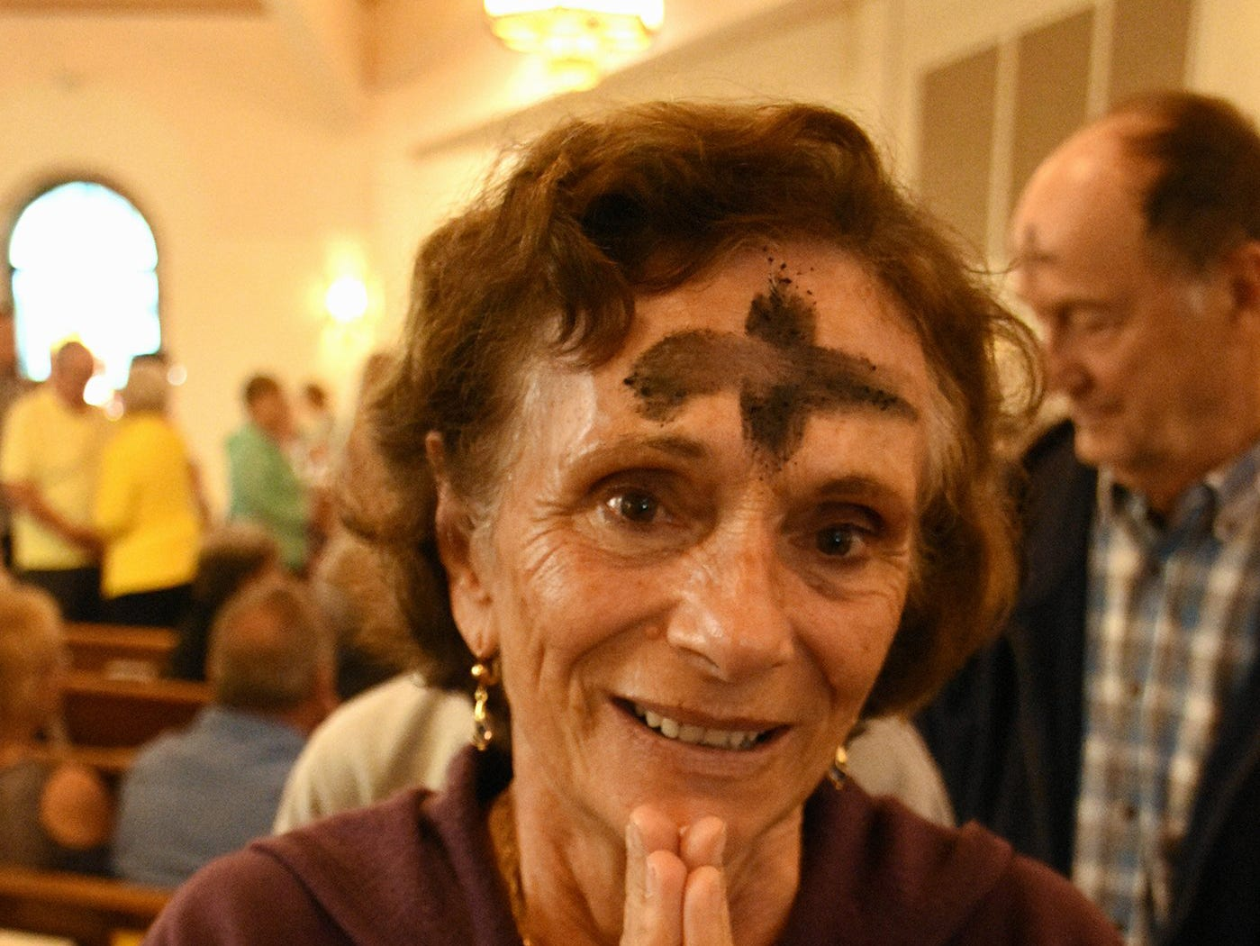 Antoinette Dotro returns to her pew after being daubed with ashes. Catholics on Marco Island and around the world, along with many other Christians, celebrated Ash Wednesday by attending mass and having a cross drawn on their foreheads in ashes.
