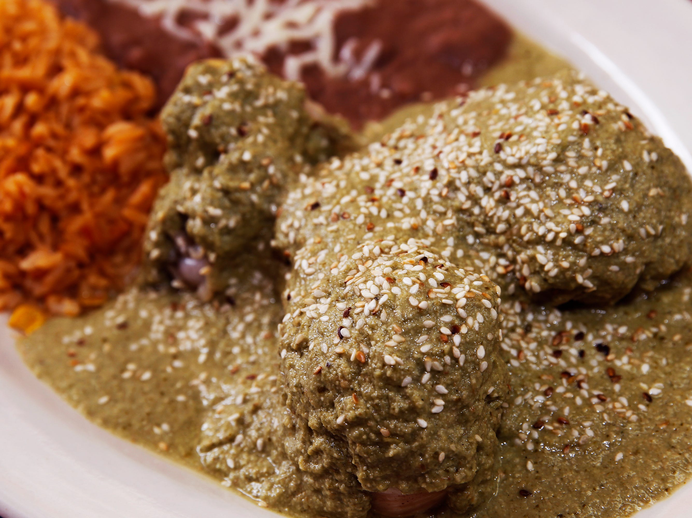 Pipian verde, sprinkled with sesame seeds, covers chicken drumstricks at El Tlaxcalteca. The pipian, made from ground pumpkin seeds, is one of several moles that the restaurant makes.