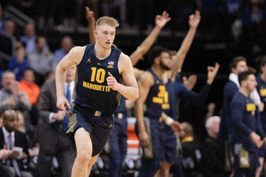 Sam Hauser heads back on defense as the Marquette bench lets everyone in the Prudential Center know he just hit a three-pointer against Seton Hall during the first half.