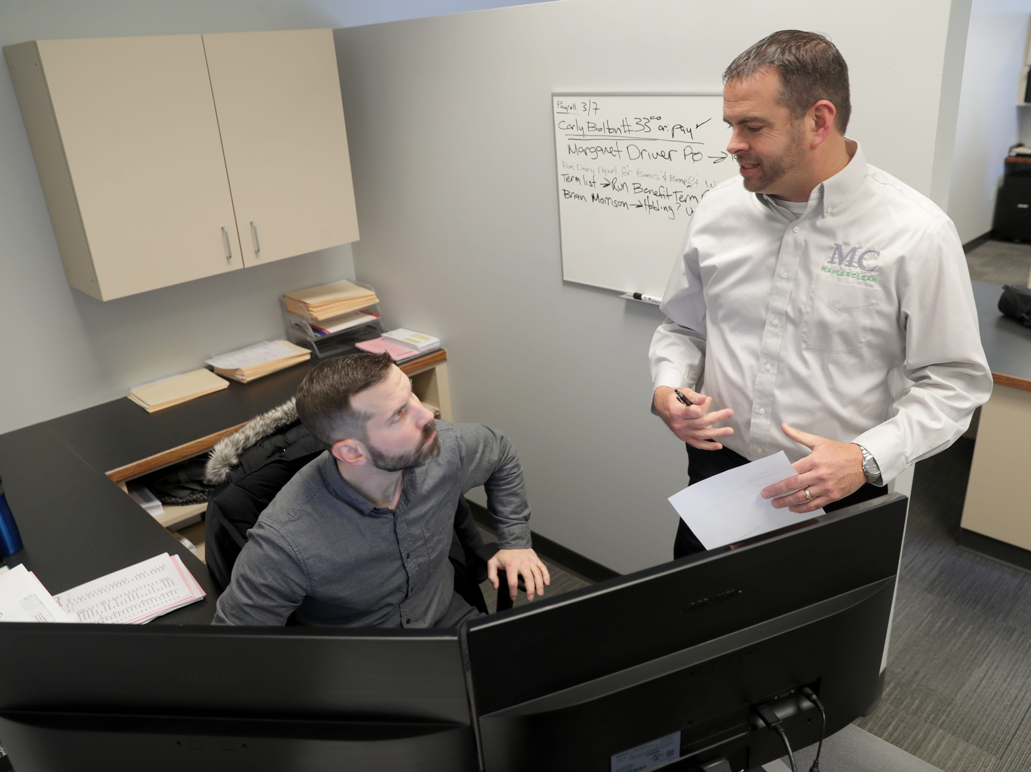 Michael Hoard (left), a MahlerClean human resource generalist, speaks with company President PatSullivan on March 6 at MahlerClean in Brookfield.