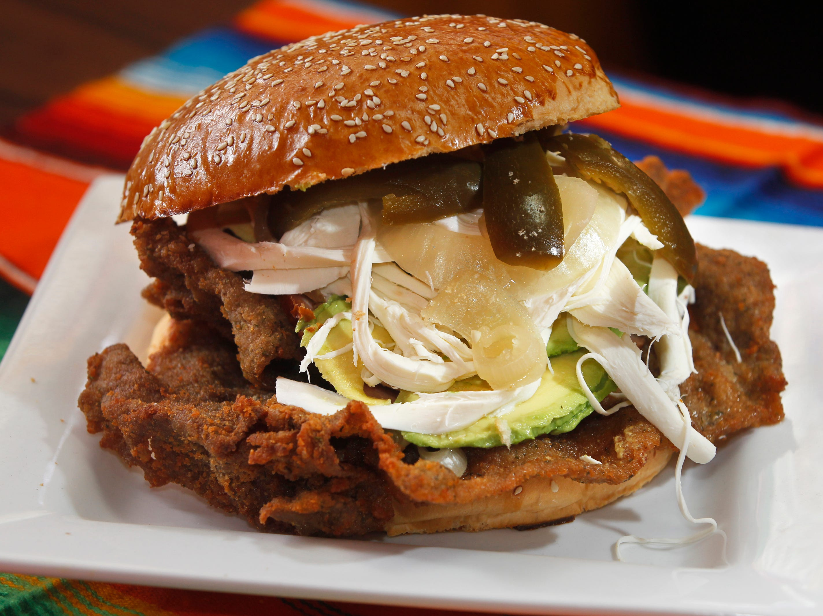 The cemita poblana starts with a seeded roll the size of a plate, and hold thin cuts of breaded chicken or beef, cheese, avocado and more.