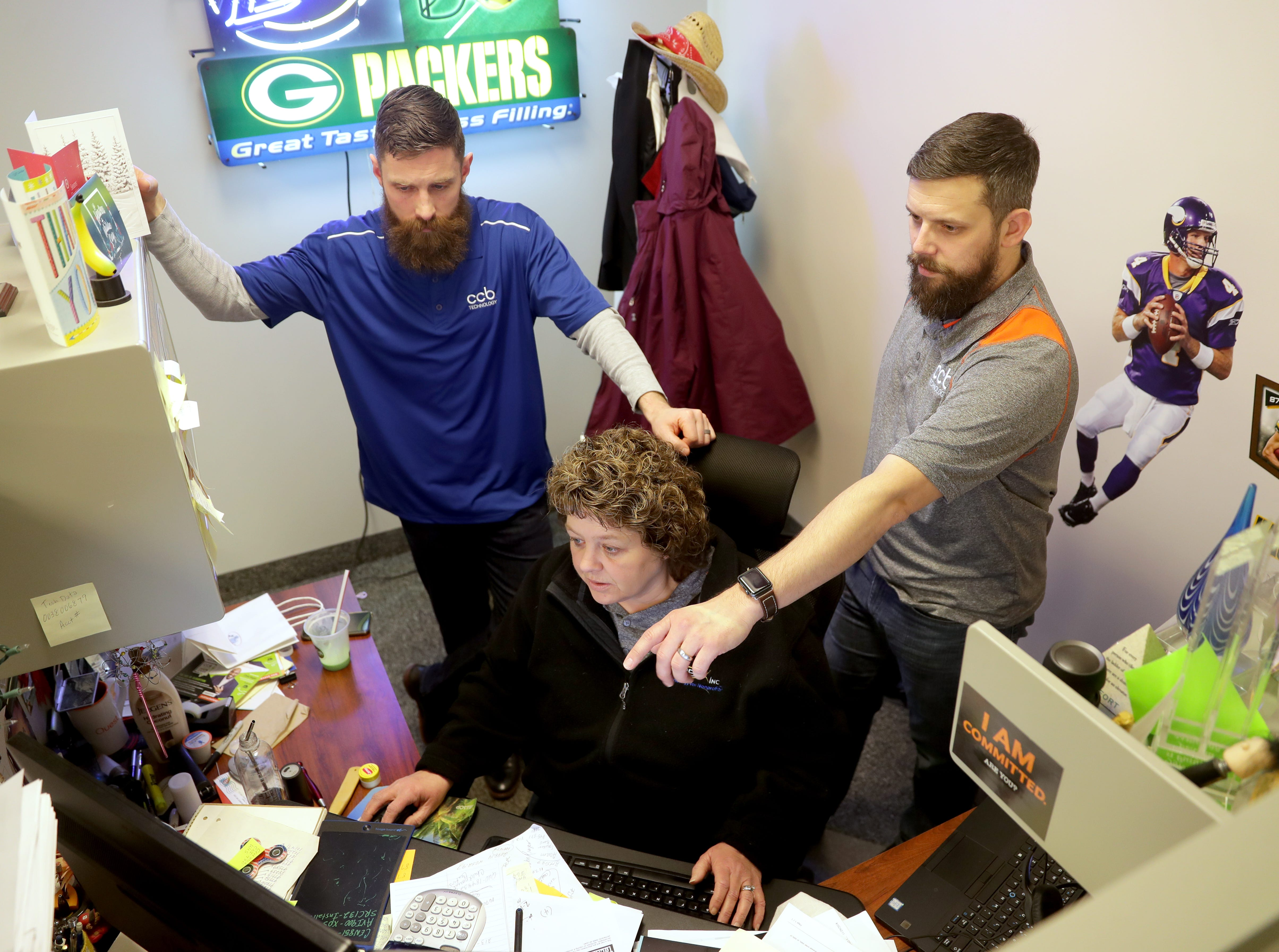 Kyle Jolly (right), director of sales, and Steve Scherer, vice president of sales, gather around Paula Rorek, national account manager, as they go over orders March 7 at CCB Technology in Racine.