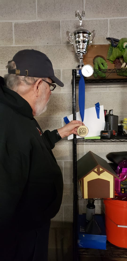 Richard Spransy of Wauwatosa proudly shows medals and trophies he won as an ice car racer.