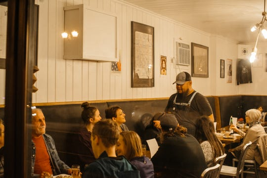 Yia Vang (in cap), who operates Union Kitchen with Chris Her, takes time to talk with diners at a pop-up dinner.