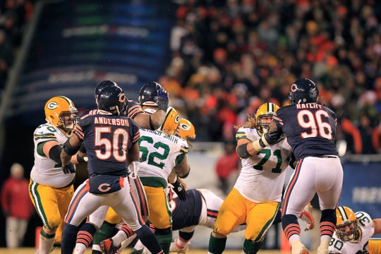 John Kuhn (30, on right) lays out after blocking Julius Peppers on a play that allowed Aaron Rodgers time to scramble and unload for a 48-yard touchdown in the final moments of the 2013 season.