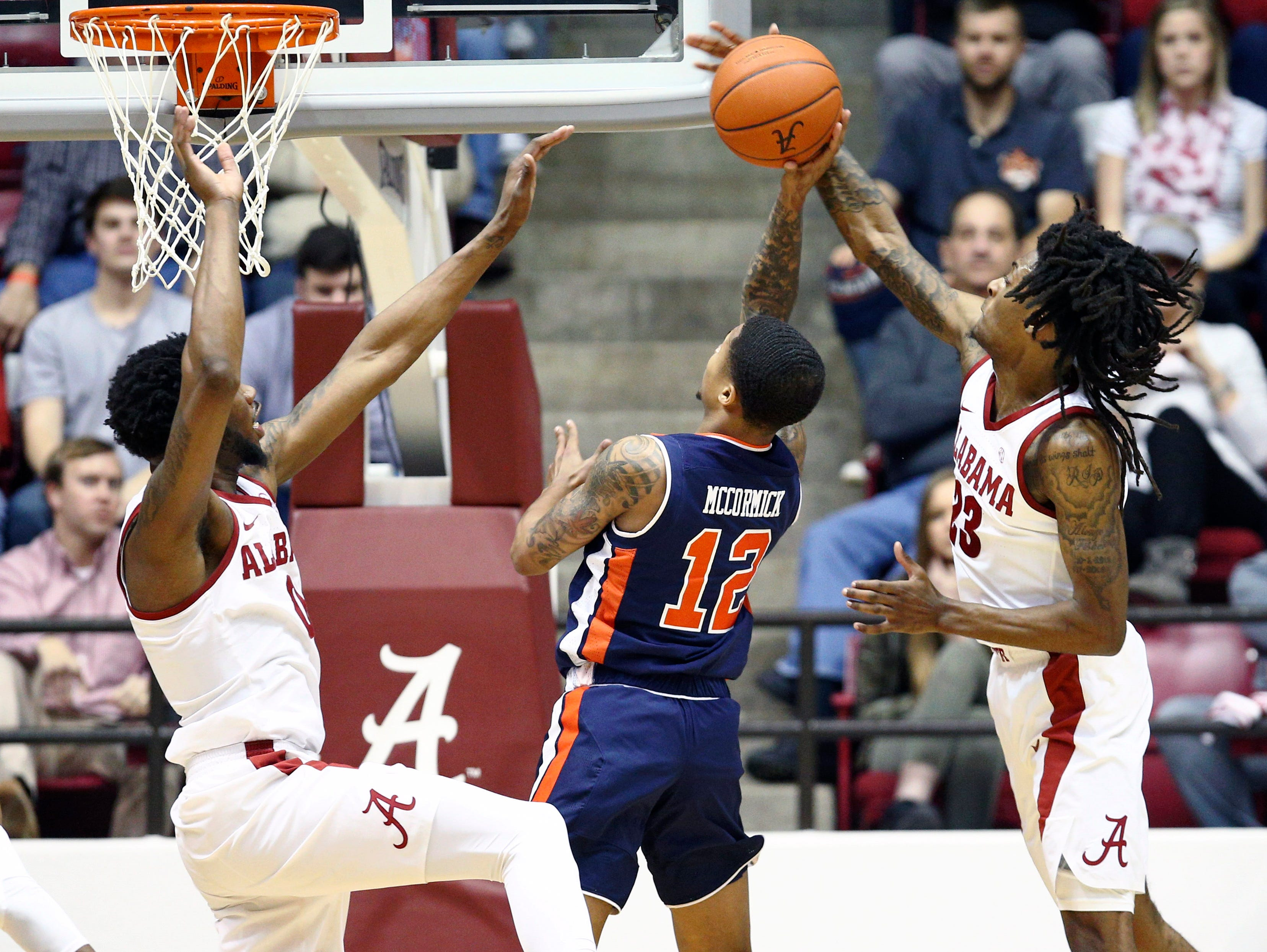 Mar 5, 2019; Tuscaloosa, AL, USA; Alabama Crimson Tide guard John Petty (23) knocks the shot of Auburn Tigers guard J'Von McCormick (12) during the second half at Coleman Coliseum. Mandatory Credit: Marvin Gentry-USA TODAY Sports