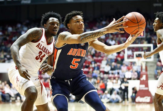 Mar 5, 2019; Tuscaloosa, AL, USA; Auburn Tigers forward Chuma Okeke (5) reaches fro the ball from Alabama Crimson Tide guard Tevin Mack (34) during the first half at Coleman Coliseum. Mandatory Credit: Marvin Gentry-USA TODAY Sports