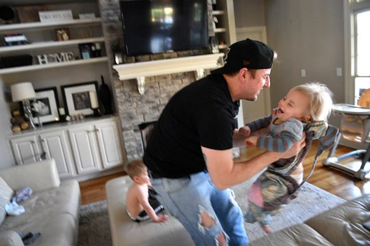 """Kent Peterson takes care of his daughter Sawyer on Feb. 13, 2019, in Franklin. He's one of two stay-at-home dads who detail crazy family stories on their """"Bring Dad a Beer"""" podcast."""