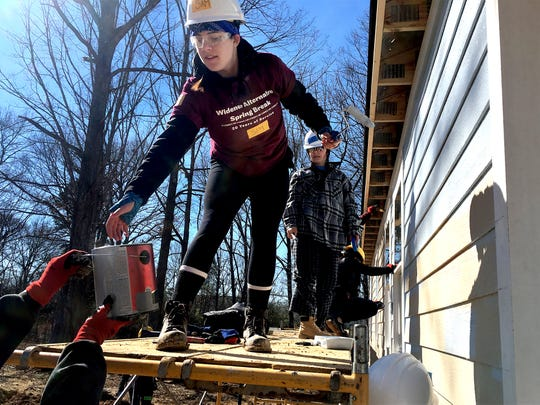 Student volunteers from Concordia University and Widener University work on a house in the upcoming Willow Crest subdivision in Fairview.