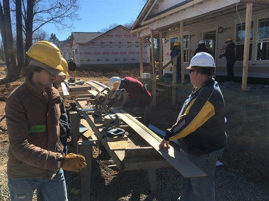 Volunteers with Habitat for Humanity Williamson-Maury cut siding for a house in the upcoming Willow Crest subdivision in Fairview.
